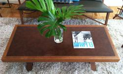 This beautifully hand-crafted, vintage coffee table has a faux-leather inlay and uniquely designed legs. Its Belgian-inspired, mid-century aesthetic will bring charm to any living or working space. Wood is in great condition and has a soft, cherry finish.