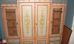 "Use in living room or bedroom. Beautiful hand-painted wardrobe / entertainment center comes with: *dresser *adjustable bookshelves *locking glass doors *fitted for TV *shelf for dvd/cable box *interior space measures 40"" across *hideaway / pocket doors"