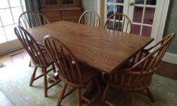 "Solid oak furniture hand-made in Wingdale, NY. One trestle table 65""w x 38""d x 30""h; Spoonback chairs with spindle construction: 6 side chairs, 2 arm chairs; 3 Bentwood stools with swiveling saddle seats 24"" high; buffet 42""w x 18""d x 32""h; corner"